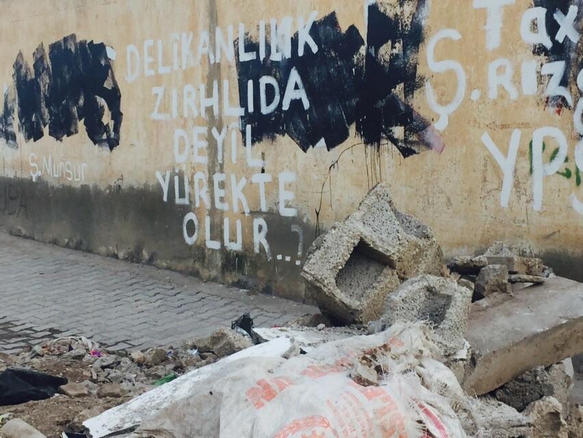 """Nusaybin'in ara sokaklarında bir duvar yazısı: """"Delikanlılık zırhlıda değil, yürekte olur"""""""