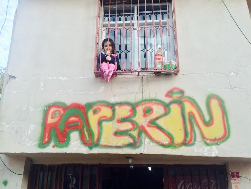 Güzel bir kız çocuğu el sallıyor, altında sarı kırmızı yeşil renklerle RAPERİN yazıyor, anlamı 'ayaklanmak', öğreniyorum ki kızın adı da Raperin...