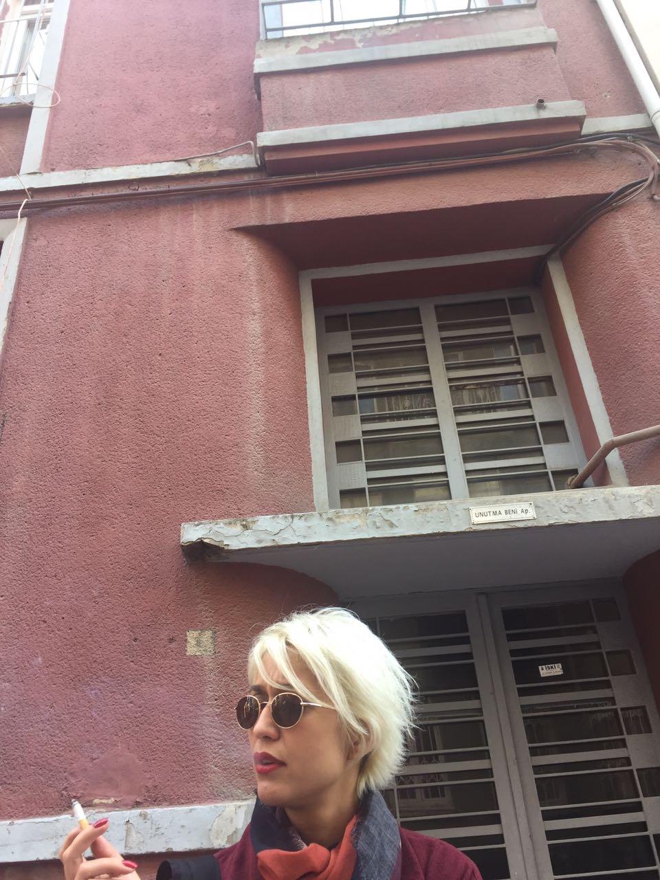 Nermin Yıldırım, ilk kitabına adını da veren İstanbul/ Cihangir'deki Unutma Beni Apartmanı önünde.