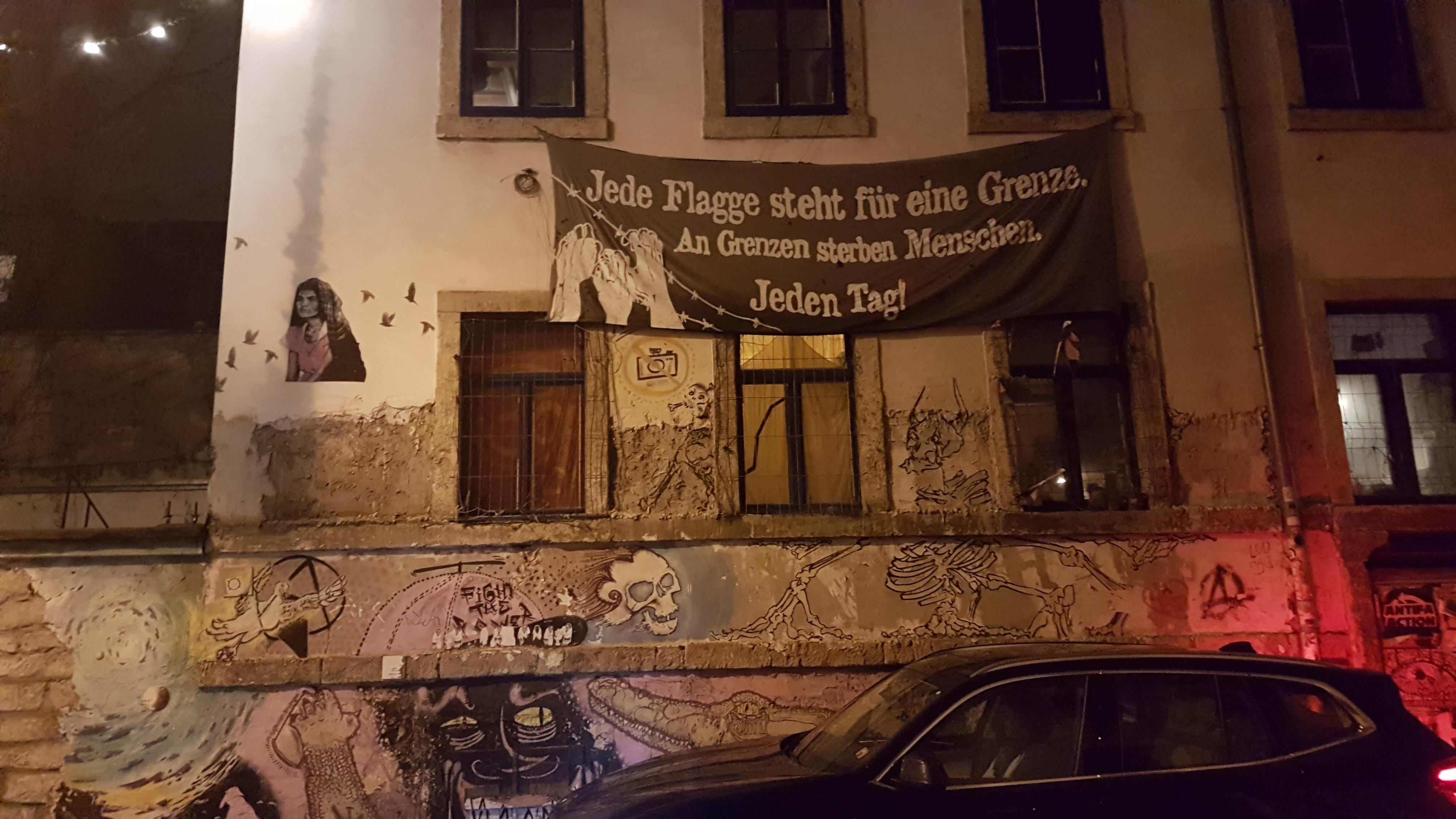 """Dresden'in Luther Caddesi üzerindeki işgal evinin boyası dökülen dış cephesini graffitiler ve mültecilerle dayanışma için asılmış """"Her bayrak bir sınırı işaretliyor. Sınırlarda insanlar ölüyor. Her gün!"""" yazılı pankart süslüyor."""